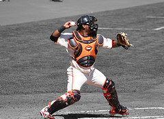 pro catcher in the bow and arrow throwing position working the 1st and 3rd defense