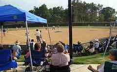 baseball parents bring their own chairs and gather round the backstop